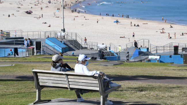 Two people wearing face masks sit on a bench overlooking Bondi Beach on Wednesday during Greater Sydney's coronavirus lockdown. Photo: James D. Morgan/Getty Images