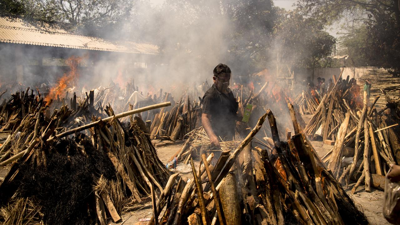 A man performs the last rites of his relative who died of COVID-19 as other funeral pyres are seen burning during a mass cremation held at a crematorium yesterday. Picture: Anindito Mukherjee/Getty Images