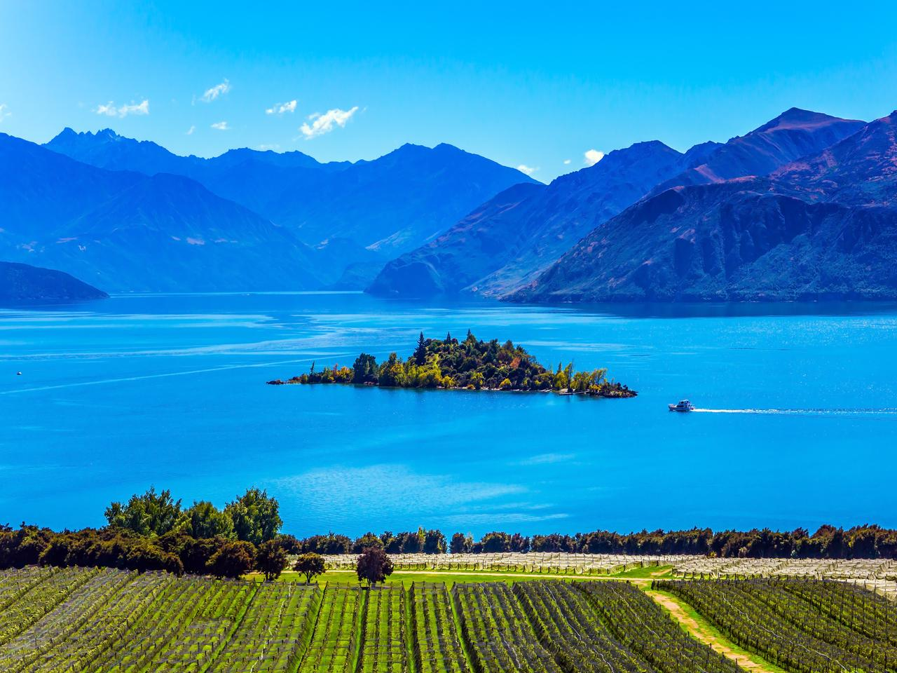 Fabulously beautiful Lake Wanaka. In the middle of the lake is a wonderful little island. Exotic journey to the South Island of New Zealand. Concept of active and ecological tourism