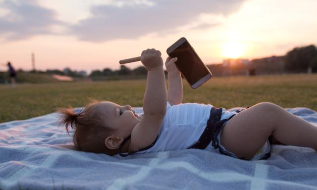 Ten months old baby girl playing with mobile phone in park on blanket on hot summer day