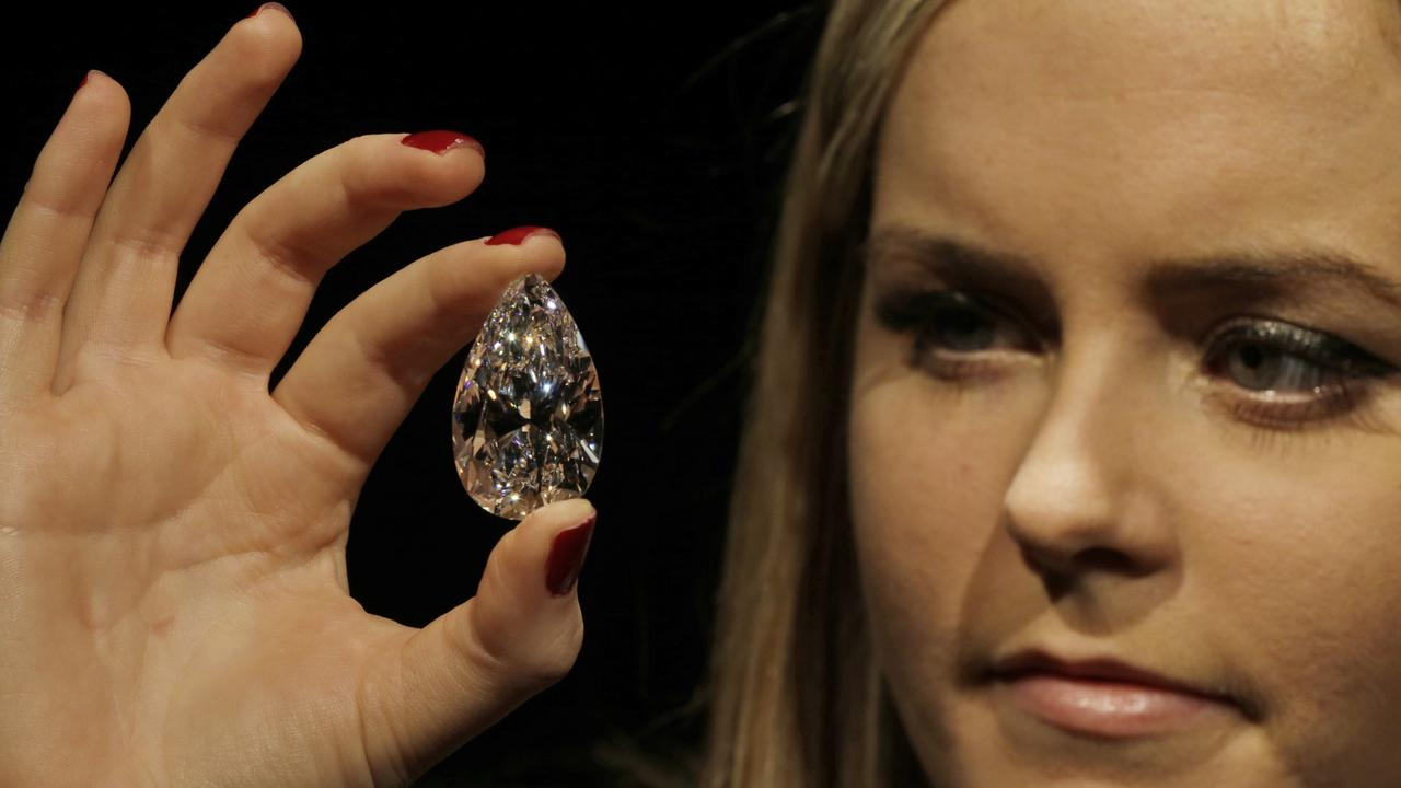An auction house employee holds a pear-shaped diamond weighing 101.73 carats, as she poses for the photographers in central London, Wednesday, March 13, 2013. Offered for sale for the first time on May 15, 2013 in Geneva, Switzerland by Christie's, the gemstone, one of the largest pear-shaped diamonds known to date, is a D colour, Type IIA Flawless gem. (AP Photo/Lefteris Pitarakis)