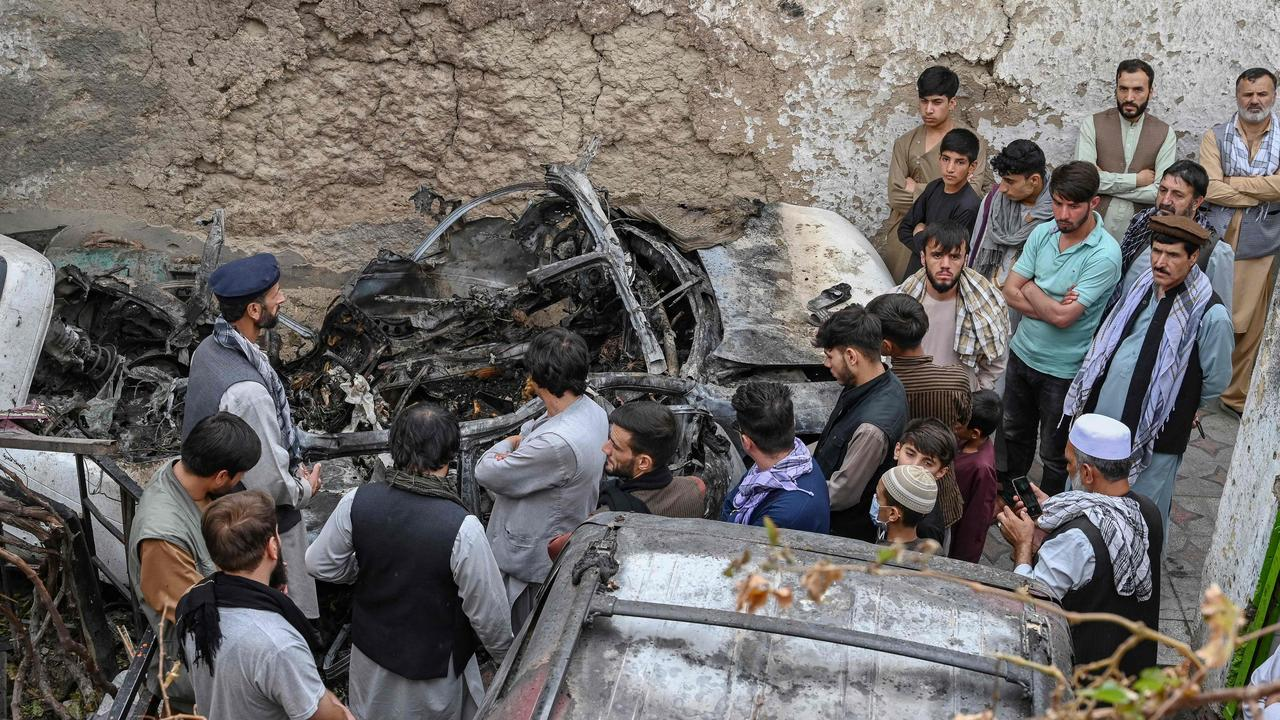 Afghan residents and family members of the victims gather next to a damaged vehicle inside a house, the day after a US drone air strike. Picture: Wakil Kohsar/AFP