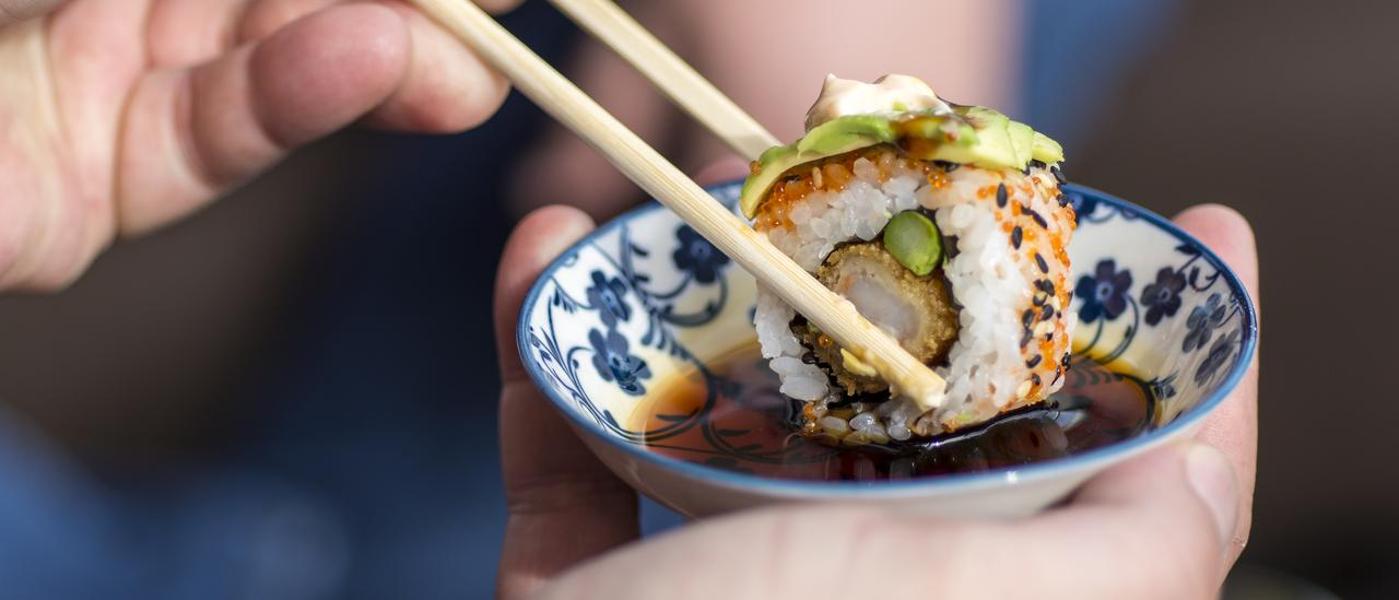 Male Hand Holding Chopsticks to Dip Sushi Roll in the Soy Sauce