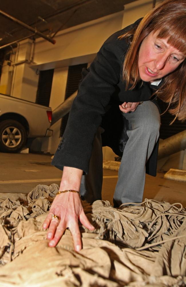 FBI Special Agent Robbie Burroughs with a parachute found in Seattle in 2008. At the time, the FBI was examining any possible links between the parachute and the DB Cooper case. Picture: AP/Kevin P. Casey