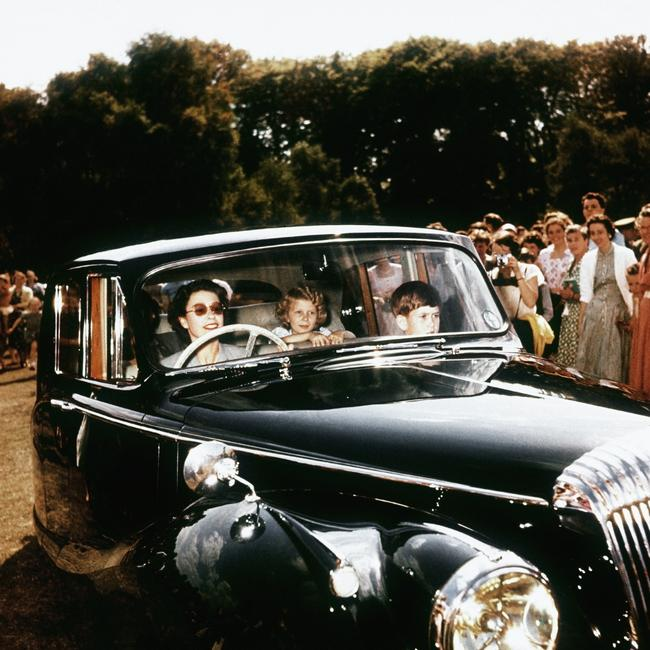 Queen Elizabeth II driving her children Prince Charles and Princess Anne at Windsor, watched by a group of onlookers in 1957. Picture: Hulton-Deutsch Collection/CORBIS/Getty Images