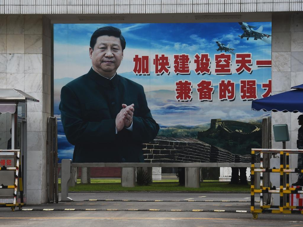 A soldier stands guard in front of a huge portrait of Chinese President Xi Jinping. The freedoms China enjoyed in the 1990s have long been unravelled, and replaced by a new dystopia. Picture: AFP