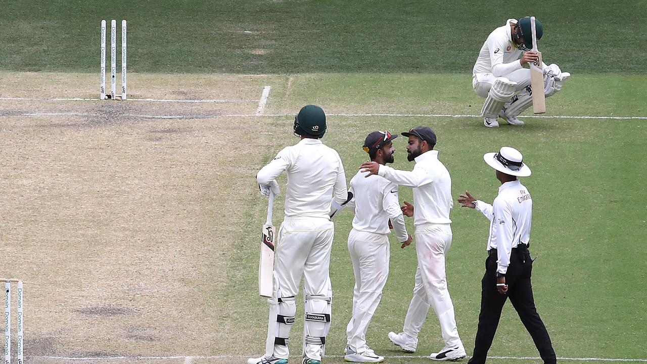 Josh Hazlewood and Nathan Lyon of Australia look dejected as Virat Kohli and Ajinkya Rahane of India celebrate after India claimed victory in the First Test. Picture: Getty Images