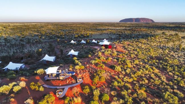Aerial view of Longitude 131 with Uluru-Kata Tjuta in the background.The best venue to watch the spectacle of Uluru is Longitude 131 with a gathering of luxury pavilions nestled among the rust-red landscape. The desert base fans out from the Dune House, site of lounging, cocktails and rock gazing.