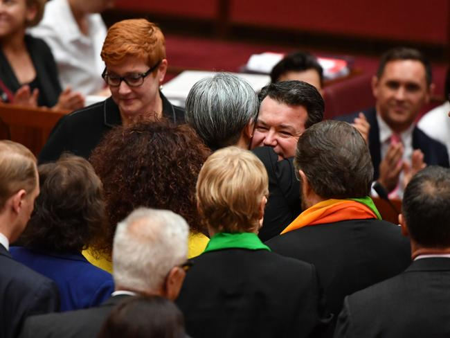 Penny Wong hugs Liberal Senator Dean Smith after the vote for the same-sex marriage bill. Picture: AAP
