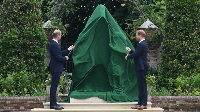 Prince William and Prince Harry remove a green cover to reveal the statue to the world. Photo: Dominic Lipinski - WPA Pool/Getty Images