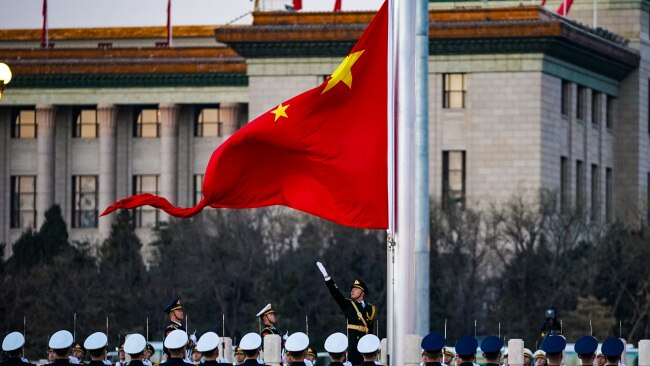 """Soldiers of the People's Liberation Army (PLA) honor guard perform the flag-raising ceremony at Tiananmen Square on New Year's Day. Beijing said it won't allow Australia to """"reap the benefits"""" from China whiling """"smearing"""" it. Picture: Getty"""