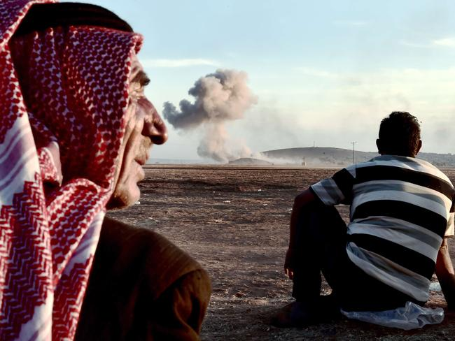 Air strikes ... People watch smoke rising from the Syrian town of Ain al-Arab, known as Kobane by the Kurds, after an air strike on the Turkish-Syrian border. Picture: AFP