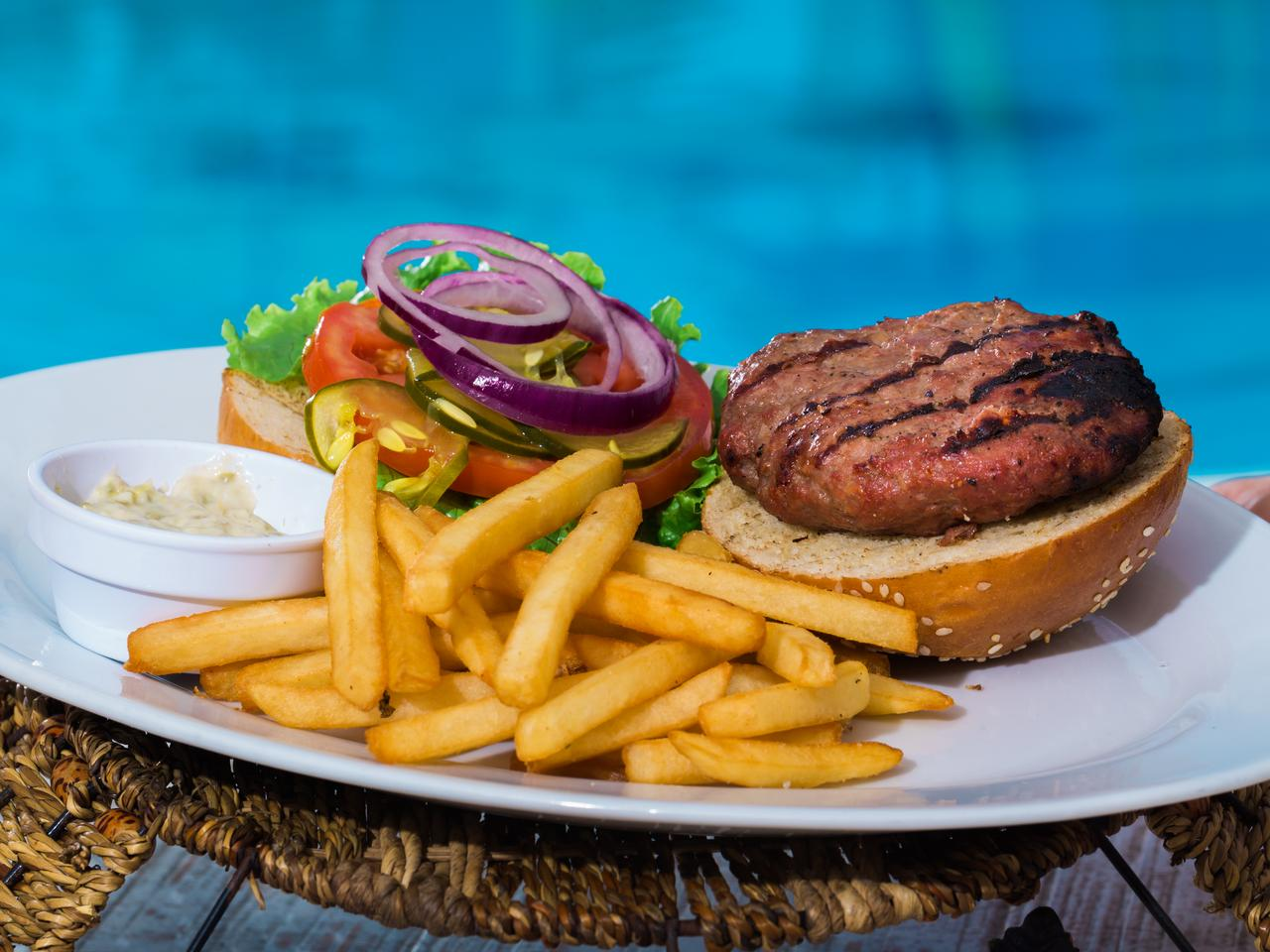 A plate with open hamburger and french fries, over a light blue swiming pool with all ingredients showing