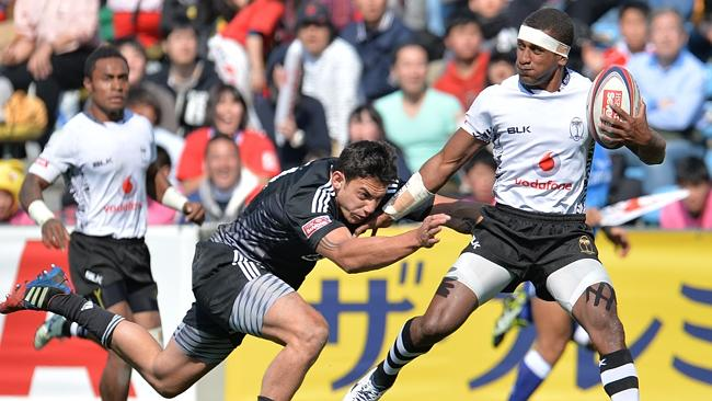 Fiji's Emosi Mulevoro (R) evades a tackle by New Zealand's Bryce Heem (L) during the 2014