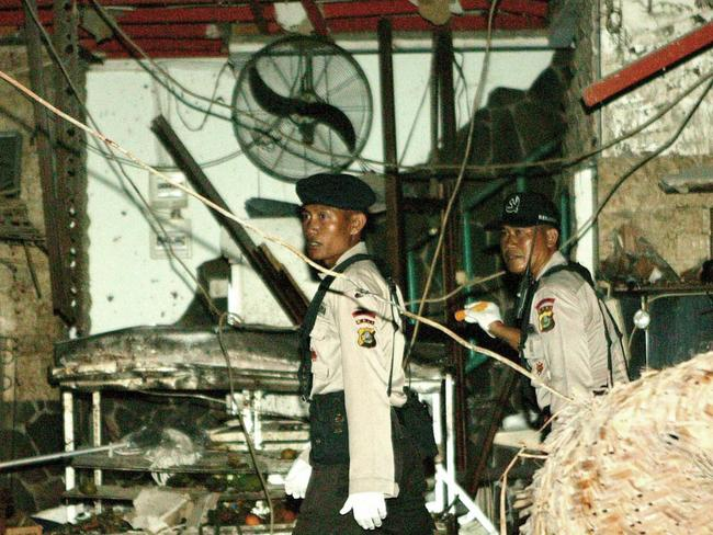 Aftermath ... Indonesian police investigate the bomb damaged site at a restaurant in Kuta.