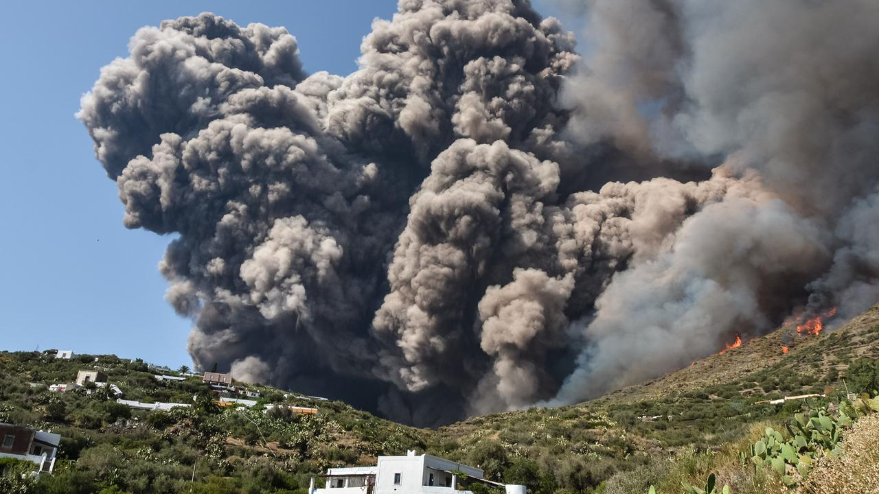 Smoke billows and flames above the hillside near house. Picture: Giovanni Isolino/AFP.