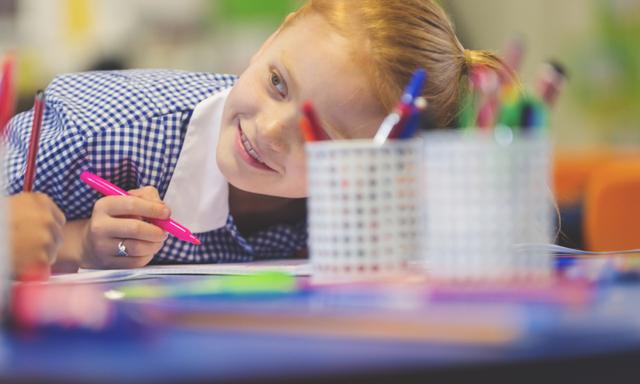 Schoolgirl working at a desk. She is wearing a school uniform. She is writing or drawing with a felt pen. She is smiling and happy having fun.