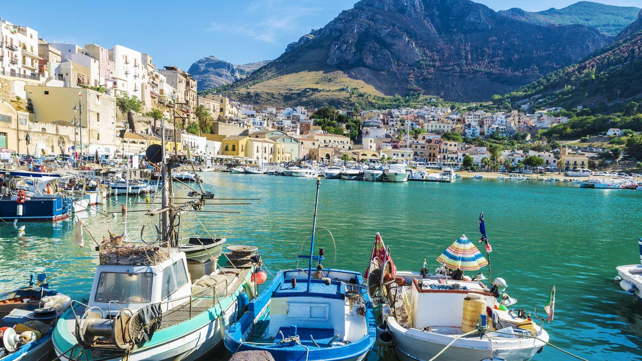 Fishing port with old wooden fishing boats docked at the marina in summer in Castellammare del Golfo in Sicily, Italy