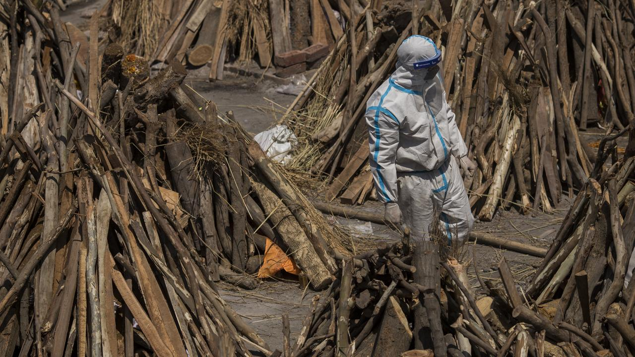 A man wearing PPE kit can be seen amid funeral pyres before they were lit to perform the last rites of the patients who died of the coronavirus. Picture: Anindito Mukherjee/Getty Images