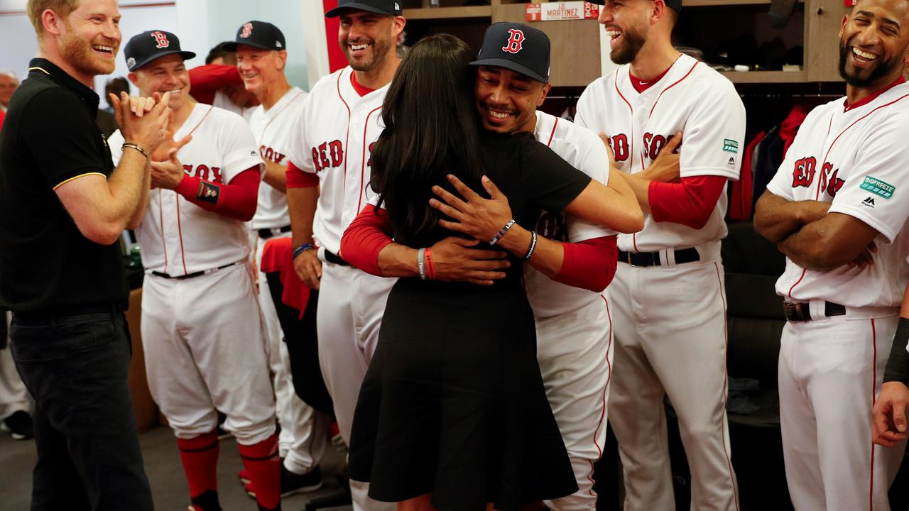 Prince Harry laughs as Meghan, Duchess of Sussex gives a special hug to one Red Sox player. Now we know why. Picture: Peter Nicholls/Pool