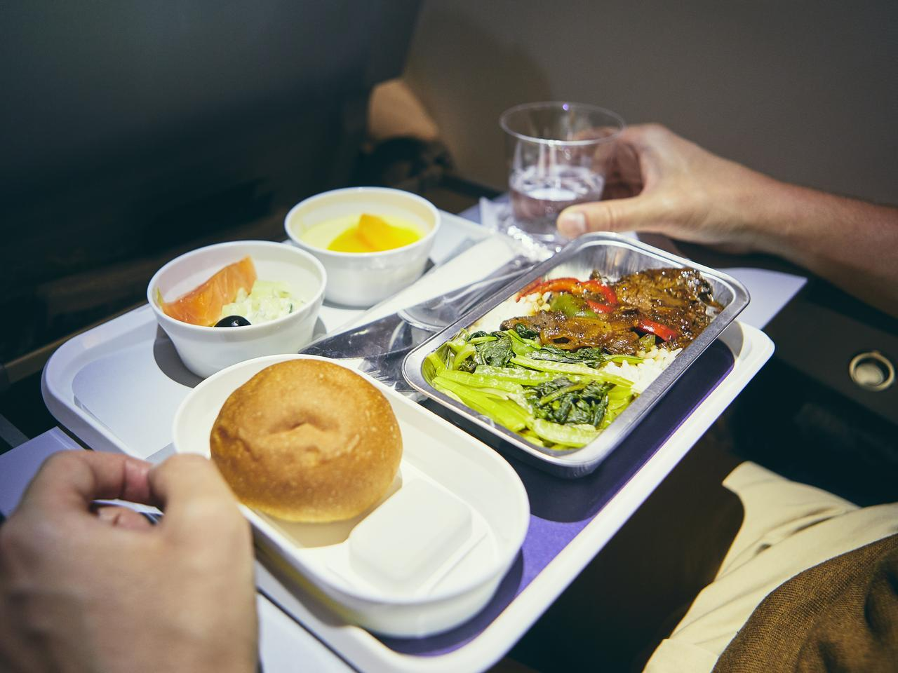 Traveling by airplane. Passenger enjoying dinner in economy class during long haul flight.