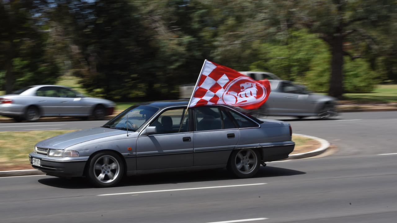 A Holden fan flies the flag on their Commodore at the closure of the Elizabeth plant. Picture: Bernard Humphreys