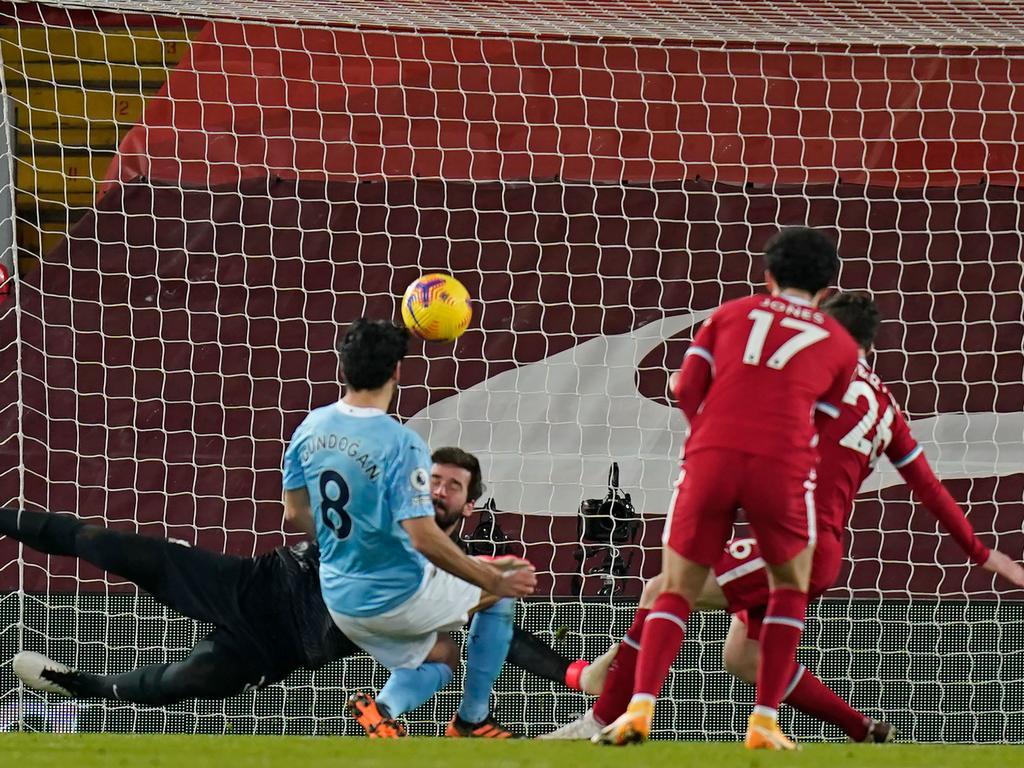 Manchester City's German midfielder Ilkay Gundogan shoots past Alisson Becker. (Photo by Tim Keeton/AFP)