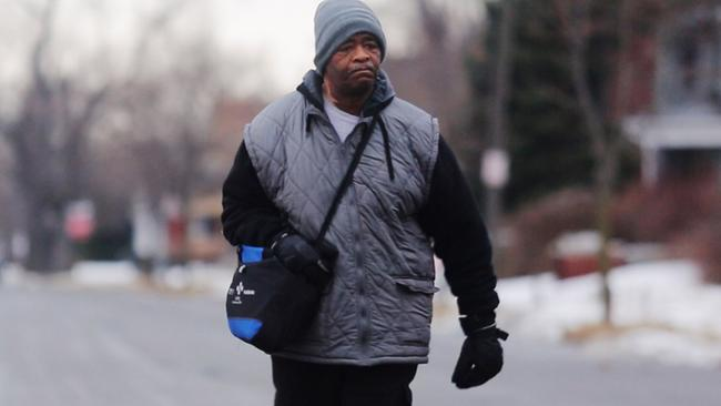 In this Jan. 29, 2015, photo, James Robertson, 56, of Detroit, walks toward Woodward Aveune in Detroit to catch his morning bus to Somerset Collection in Troy before walking to his job at Schain Mold & Engineering in Rochester Hills. Getting to and from his factory job 23 miles away in Rochester Hills, he'll take a bus partway there and partway home and walk 21 miles according to the Detroit Free Press. (AP Photo/Detroit Free Press, Ryan Garza) DETROIT NEWS OUT; NO SALES
