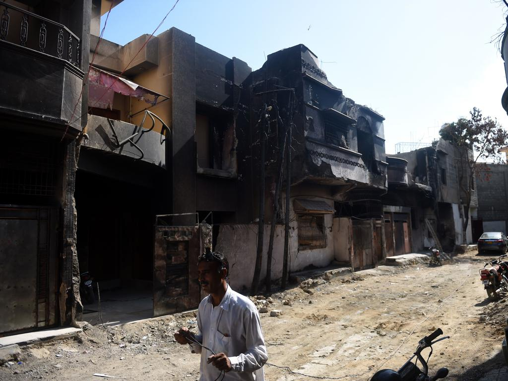 A man walks past houses still damaged from the crash. Picture: Rizwan Tabassum/AFP