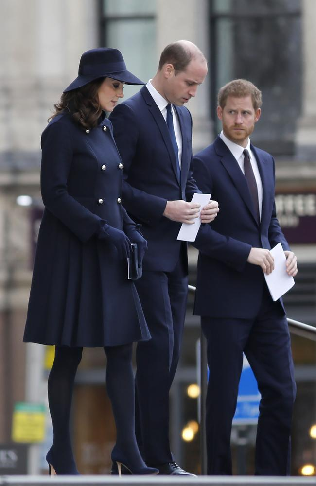 Kate Middleton with Prince William and Prince Harry braving the cold in a navy coat. Image: / AFP PHOTO / Tolga AKMEN.