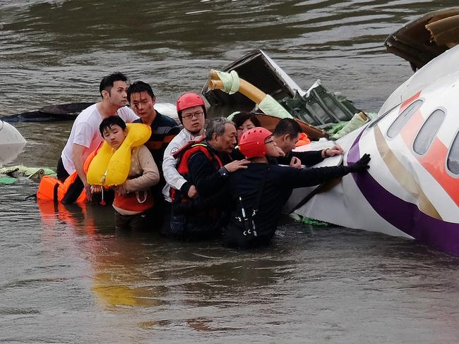 Saved ... Rescue personnel (in helmets) help passengers as they wait to be transported to land from the wreckage of a TransAsia ATR 72-600 turboprop plane that crash-landed into the Keelung river in New Taipei City. Picture: AFP / SAM YEH
