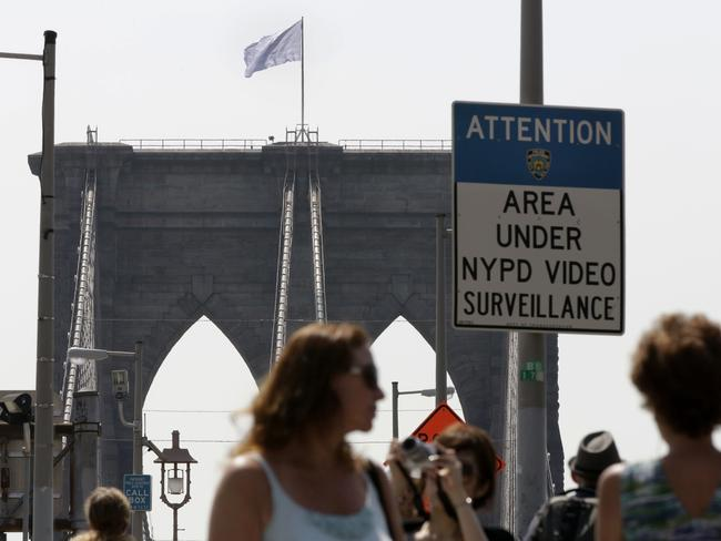Mystery ... police crime scene and intelligence detectives are still investigating how the flags were switched out on the famed span that connects Brooklyn and Manhattan. Picture: Richard Drew
