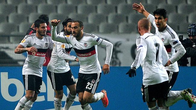 Besiktas' Cenk Tosun celebrates with teammates after scoring against Tottenham.