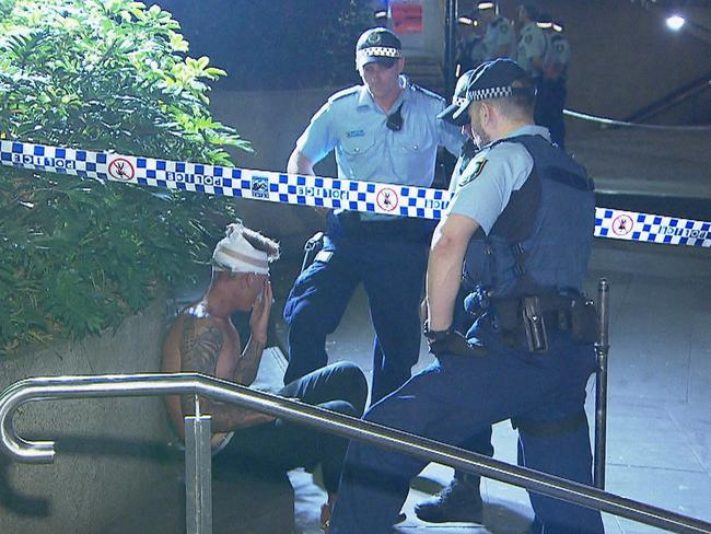 An injured man speaks to police following the brawl. Picture: Daniel Shaw