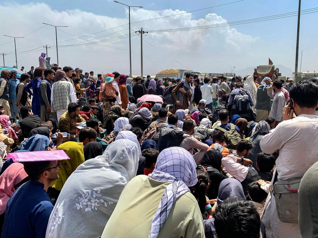 Afghan people gather along a road as they wait to board a U S military aircraft to leave the country. Picture: Wakil Kohsar/AFP