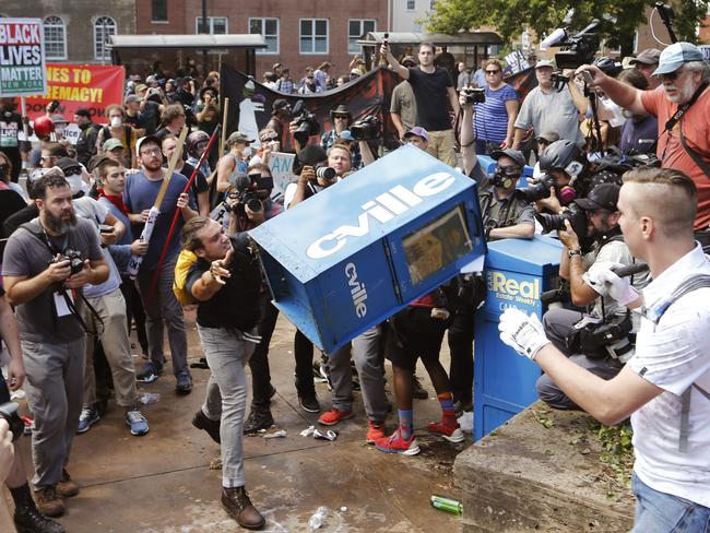 White nationalist demonstrators clash with a counter-demonstrator as he throws a newspaper box at the entrance to Lee Park in Charlottesville, Virginia on Saturday. Picture: AP Photo/Steve Helber