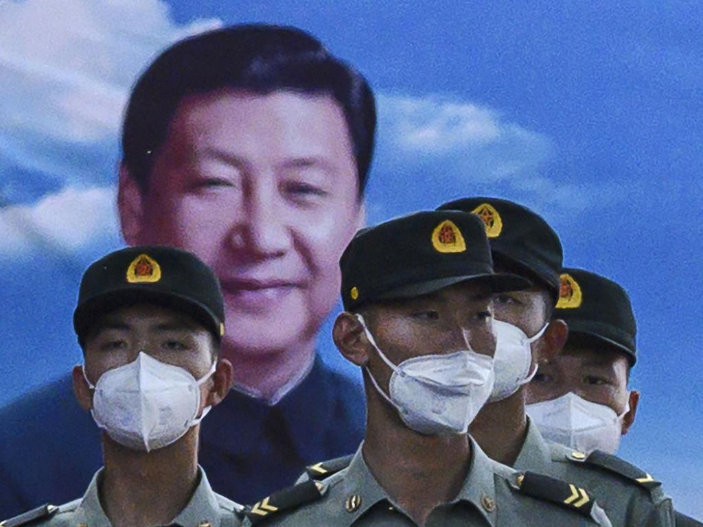 Soldiers of the People's Liberation Army's Honour Guard Battalion stand at attention in front of photo of China's president Xi Jinping at their barracks outside the Forbidden City, near Tiananmen Square. Picture: Kevin Frayer / Getty Images