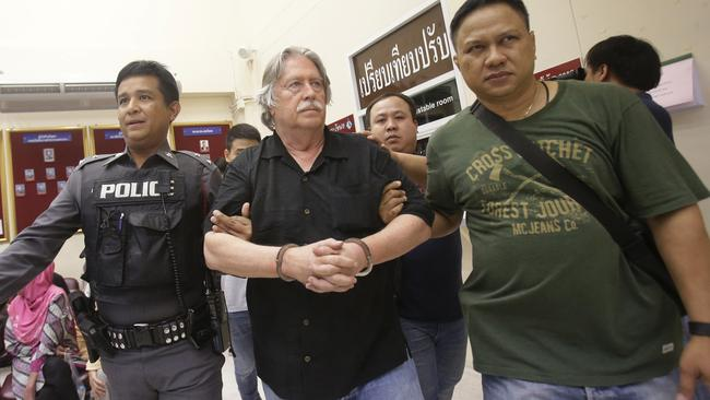 Thai police escort suspect, American James Eger, 66, charged with trafficking in forged passports and concealing a dismembered corpse at a Bangkok apartment. Picture: AP/Sakchai Lalit