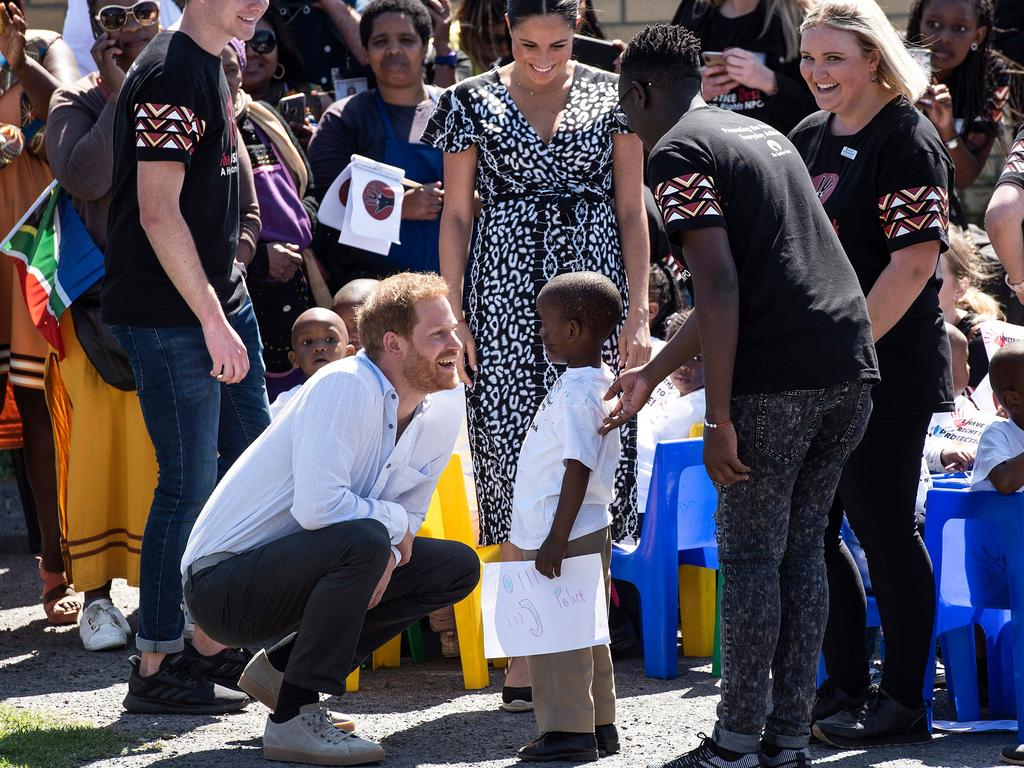 The boy gave a gift to the Duke and Duchess of Sussex as they arrived at Justice desk. Picture: David Harrison/AFP