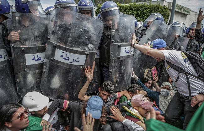 First prize in the Spot News Singles category: Students scuffle with riot police during an anti-government demonstration in Algiers, Algeria. Picture: Farouk Batiche, Deutsche Presse-Agentur, World Press Photo via AP