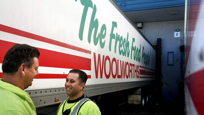 Workers stand next to a truck at the Woolworths Ltd. Minchinbury Distribution Centre in Sydney May 24 2007 : PicGrant/Turner /Bloomberg /News - companies food supermarket logos transport safety clothing refelctive vest