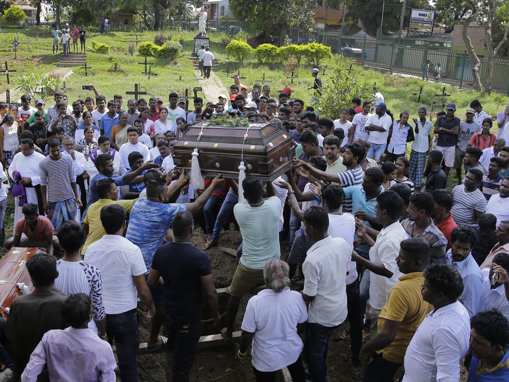 Sri Lankans prepare to bury the coffins carrying remains of Berington Joseph and Burlington Bevon, who were killed in the Easter Sunday bombings. Picture: AP