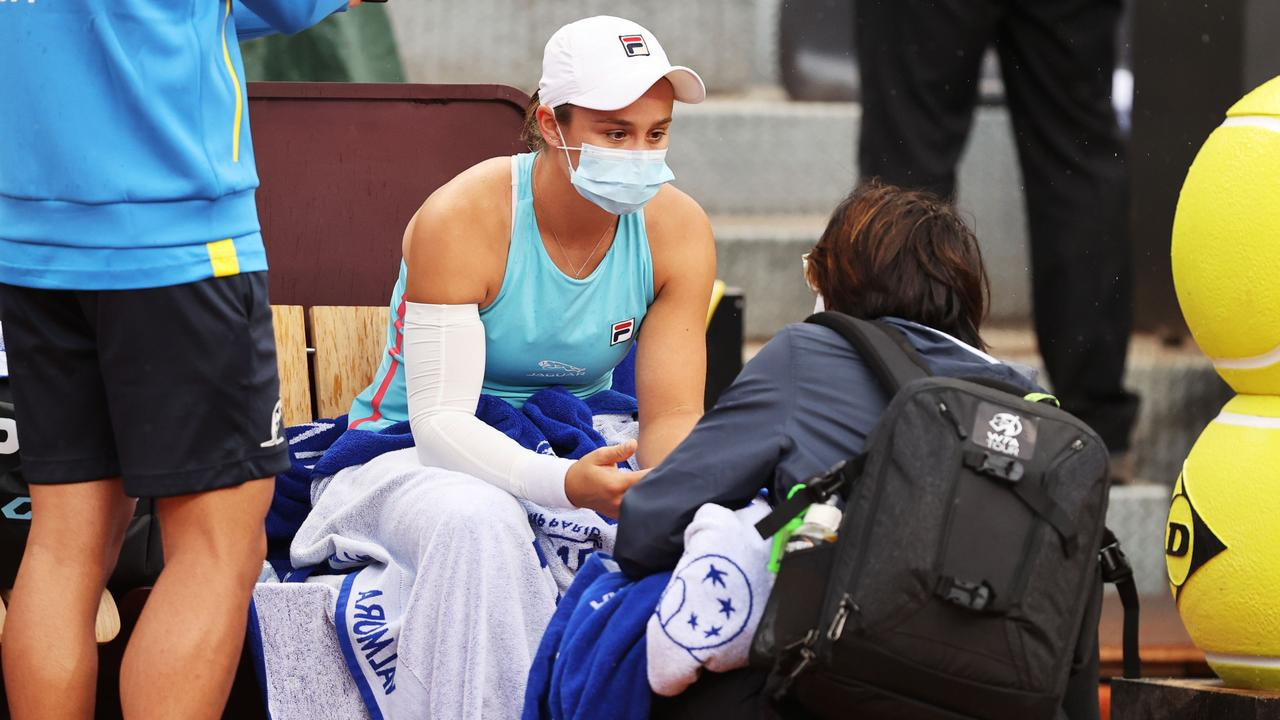 Ash Barty chats to the trainer before retiring hurt while playing Coco Gauff. (Photo by Clive Brunskill/Getty Images)