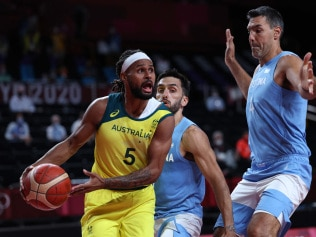 Australia's Patty Mills (L) handles the ball past Argentina's Facundo Campazzo (C) and Luis Scola in the men's quarter-final basketball match between Australia and Argentina during the Tokyo 2020 Olympic Games at the Saitama Super Arena in Saitama on August 3, 2021. (Photo by Thomas COEX / AFP)
