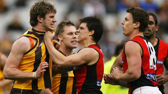 Hawthorn's Grant Birchall (left) wants a piece of Matthew Lloyd after the Essendon forward bowled over Brad Sewell in 2009.