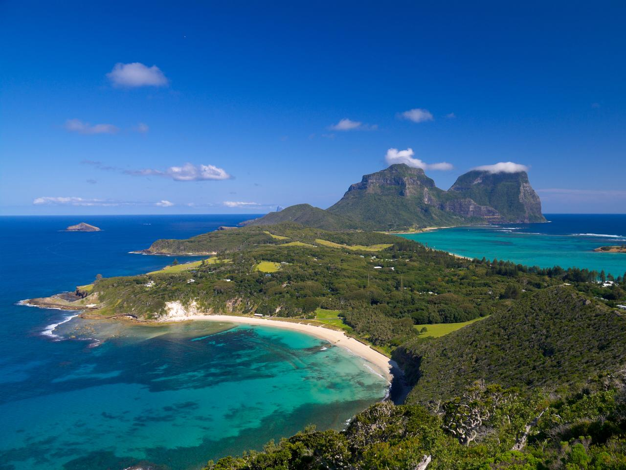 View south over the stunningly beautiful Lord Howe Island from Malabar lookout. Lagoons on both sides of the island are visible, as well as the peaks of Mts Lidgbird and Gower at the far end of the island. The sky and ocean are brilliant blue.