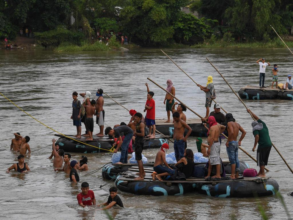 Honduran migrants heading in a caravan to the US wait for fellow migrants to jump from the Guatemala-Mexico international border bridge and swim to Mexico. Picture: AFP