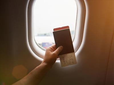 Hand holding passport with airplane ticket on plane window sunny background