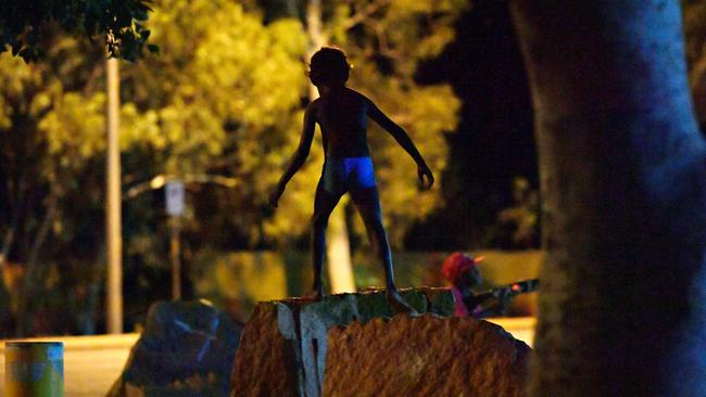 A young child plays as his family sit beside the road near the BP service station in Tennant Creek after 10pm.