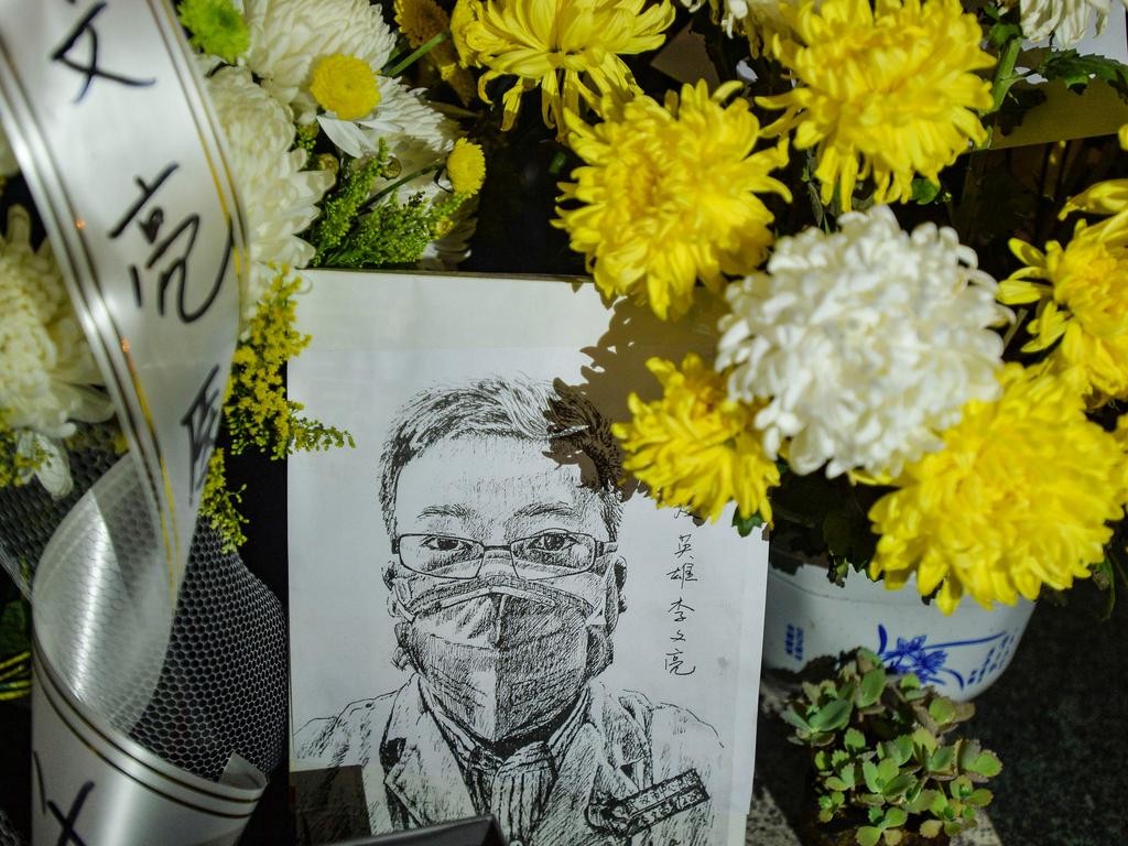 Flower bouquets were placed in tribute around an artwork of the late ophthalmologist at the Houhu Branch of Wuhan Central Hospital. Picture: STR/AFP.